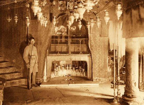 Un uomo in armi monta la guardia d'onore nella grotta della Natività custodita sotto il pavimento della basilica.