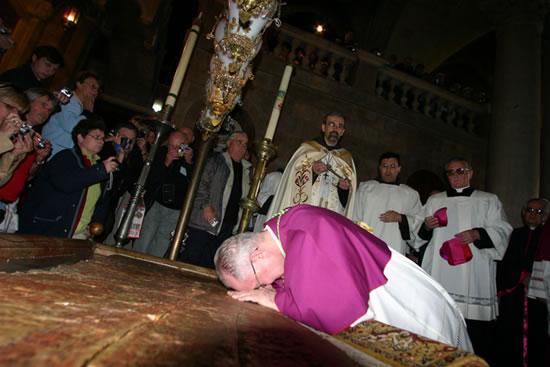 Basilica del Santo Sepolcro. Mons. Antonio Franco prostrato sulla Pietra dell'unzione. In piedi il padre Custode.