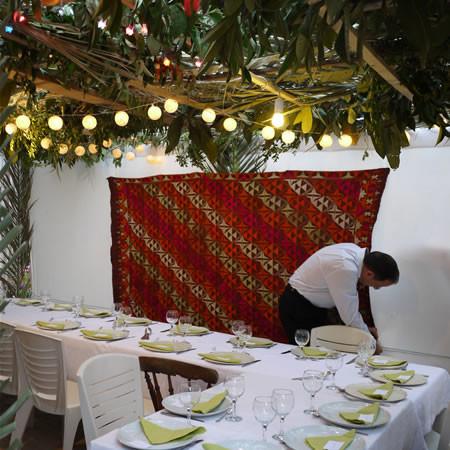 Un cameriere dà gli ultimi ritocchi alla capanna del suo ristorante.