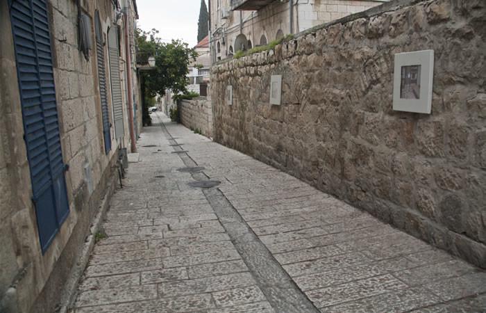 Una via del quartiere, con quadri appesi lungo il muro di cinta di una casa.
