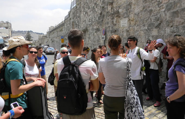 Lungo le mura di Gerusalemme, don Bortolo (in camicia bianca) con i giovani del coro. (foto S. Clementi)