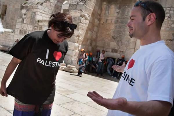 Una turista indossa la maglietta offertale da uno dei promotori della campagna <i>I love Palestine.</i>