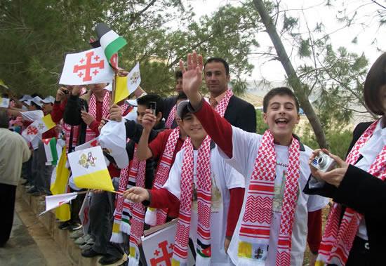 Ragazzini giordani con al collo una<i> keffiah</i> bordata dalle bandiere di Vaticano e Giordania.