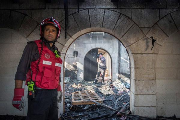 I vigili del fuoco ispezionano gli ambienti devastati dall'incendio.