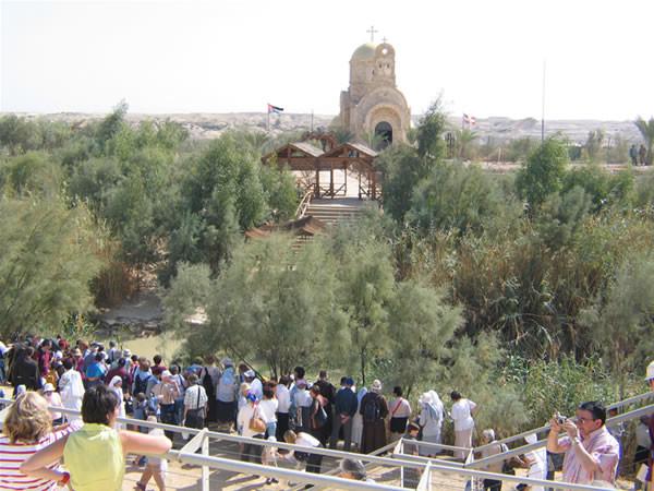 Fedeli e turisti sulla riva occidentale del Giordano, nel luogo che ricorda il battesimo di Gesù da parte di san Giovanni Battista.