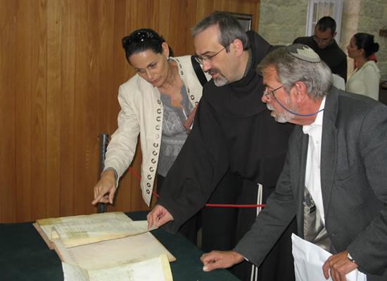 Padre Pizzaballa mostra un antico registro dei pellegrini alla signora Yisca Harani e a Daniel Rossing, direttore esecutivo del Jcjcr.