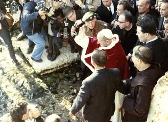 A Tabgha, in Galilea, Paolo VI è attorniato da una calca di fotografi mentre benedice le acque del Lago di Tiberiade.