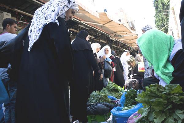 Le donne al mercato acquistano verdure per la cena serale.