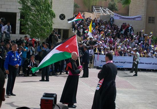 Amman, Centro Regina Pacis, 8 maggio. Il vicario patriarcale mons. Salim Sayegh si appresta ad accogliere il Papa brandendo la bandiera giordana.