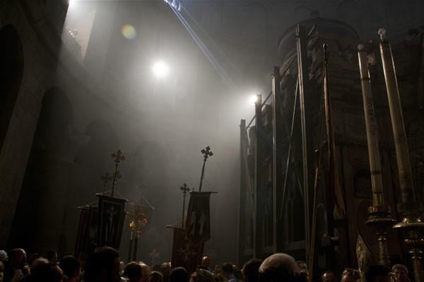 Un fascio di luce penetra dall'alto verso l'edicola che racchiude il sepolcro di Cristo. All'interno è in preghiera il patriarca greco-ortodosso.