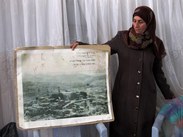 Nawal Barakat, direttrice dell'associazione femminista del villaggio, mostra una foto d'epoca di Nabi Samuel.