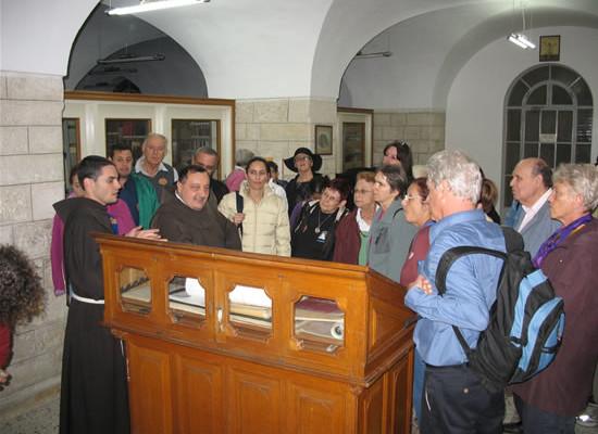 Accompagnato dal giovane fra Carlos Thomas, un gruppo visita la biblioteca custodiale e incontra il bibliotecario fra Marcello Badalamenti.