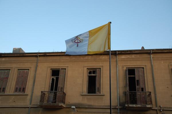La bandiera vaticana si staglia sulla facciata dell'edificio di fronte al convento, danneggiato nella guerra civile degli anni Sessanta-Settanta del secolo scorso.