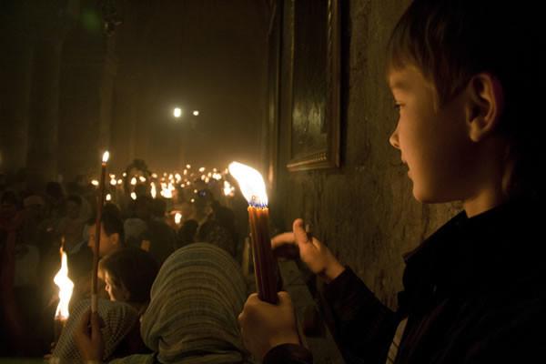 Le fiammelle accendono via via i fasci di candele recati dai fedeli, giunti da varie parti del mondo.
