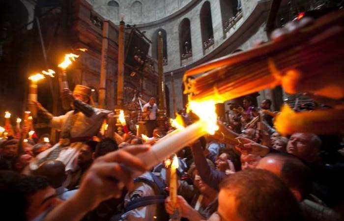 La fiamma accesa dal Fuoco Santo si diffonde tra i presenti nell'Anastasis, il cuore della basilica. (foto Marie-Armelle Beaulieu/CTS)