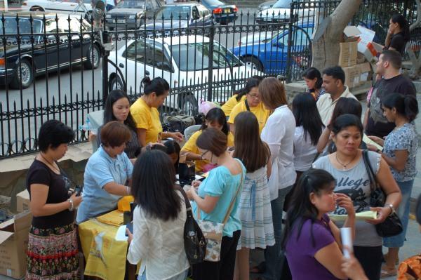 Fedeli filippine si dedicano alla vendita dei ricordi della visita papale davanti alla chiesa della Santa Croce.