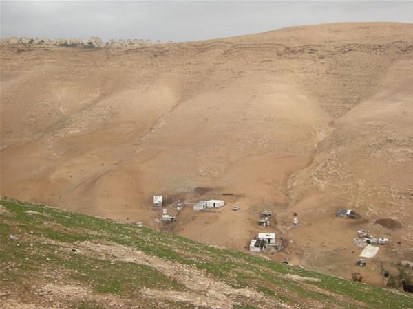 Sul ciglio di una delle colline sovrastanti s'affaccia (in alto a sin. nella foto) l'insediamento israeliano di Ma'ale Adumim.
