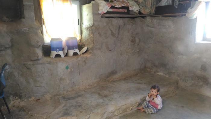 Un bambino nella spoglia casa della sua famiglia.