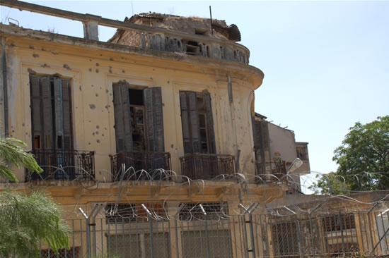 La facciata di una casa crivellata di colpi d'arma da fuoco, oltre la cinta del convento.