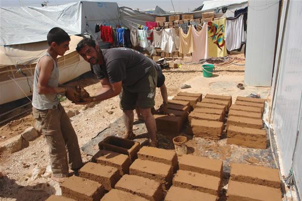Alcuni rifugiati del campo di Zaatari lavorano alla produzione artigianale di mattoni, per costruirsi una casa. (foto di C. Giorgi) [1/3]