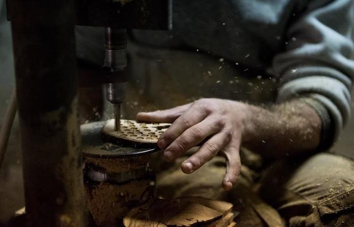 Una sezione di tronco d'ulivo viene lavorata per ricavarne le sfere.