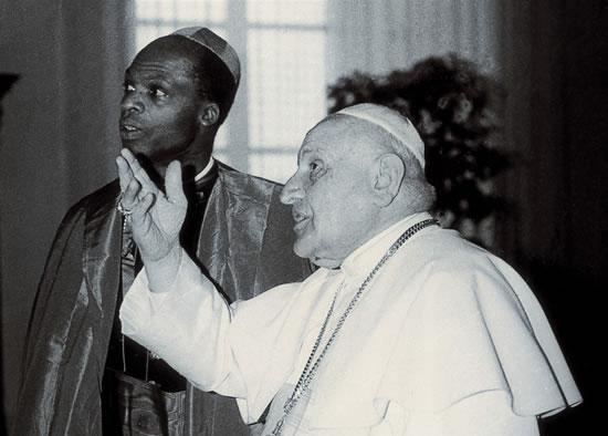 Giovanni XXIII in Vaticano conversa con un vescovo di origini africane.