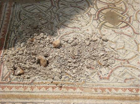 Nel dettaglio, alcuni dei danni prodotti ai mosaici a colpi di pietra.