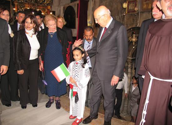 Betlemme, 27 novembre 2008. Il presidente della Repubblica, Giorgio Napolitano, nella basilica della Natività. Con la moglie Clio accoglie l'omaggio di una piccola palestinese. Accanto alla signora Clio il ministro palestinese del Turismo, Khouloud Daibes.