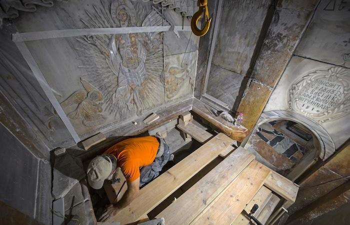 Un restauratore ripulisce la pietra venerata come letto sepolcrale del Signore Gesù. (foto Oded Balilty/ AP - National Geographic)