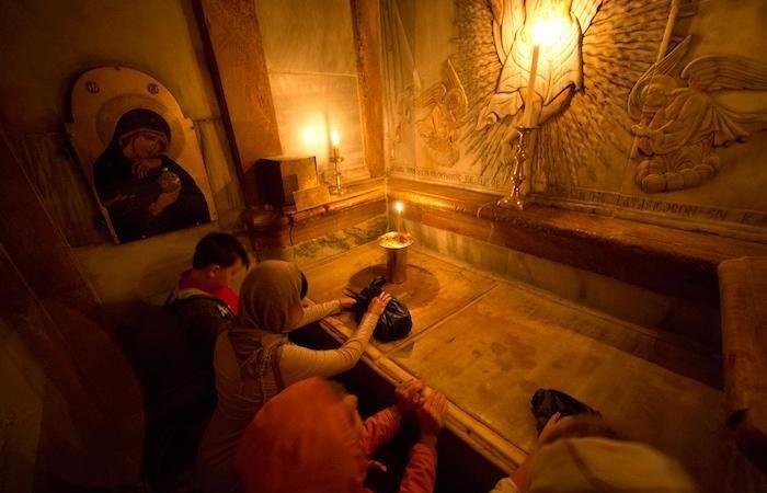 Fedeli inginocchiate in preghiera nell'edicola del Santo Sepolcro a Gerusalemme. (foto Oded Balilty/ AP - National Geographic)