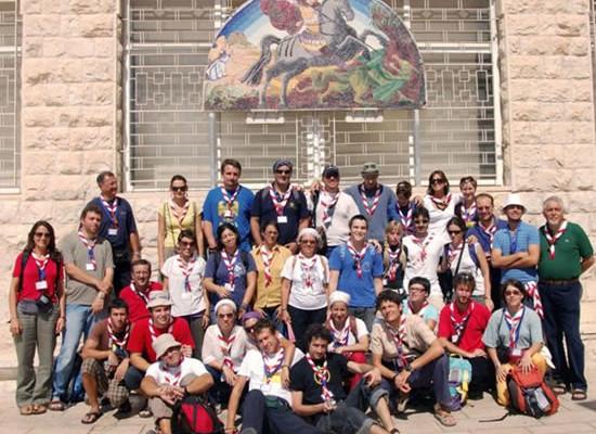 Il gruppo di<i> scout </i>a Nazaret posa sotto un'immagine di san Giorgio.