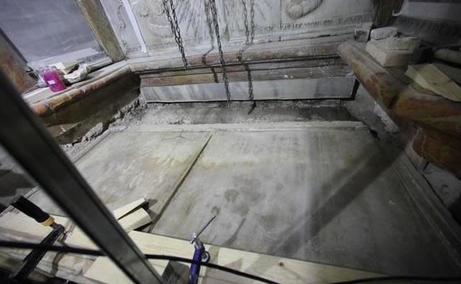 La lastra marmorea che sigilla la tomba, e funge da altare, viene rimossa per il restauro.