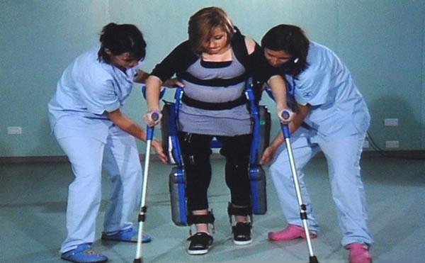 Una paziente paraplegica assistita da personale sanitario mentre impara ad utilizzare l'esoscheletro robotizzato.
