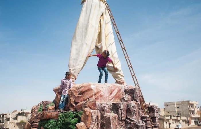 Due ragazzi giocano sul basamento del monumento alle Martiri della battaglia di Kobane. (foto Linda Dorigo)