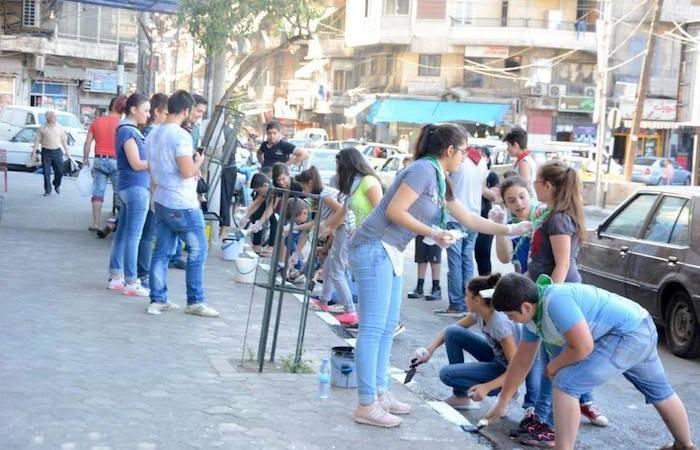 Giovani e ragazzi della parrocchia di San Francesco d'Assisi ad Aleppo ritinteggiano i marciapiedi del quartiere.