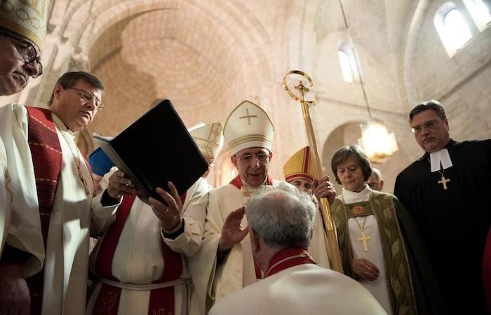 Il nuovo vescovo, in ginocchio, sta per essere consacrato.