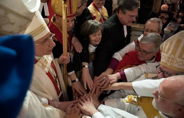 I vescovi concelebranti impongono le mani contemporaneamente sul pastore Azar.