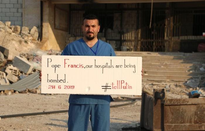 «Papa Francesco, i nostri ospedali vengono bombardati. Lo dica a Putin», recita il cartello retto da un operatore sanitario del governatorato siriano di Idlib.
