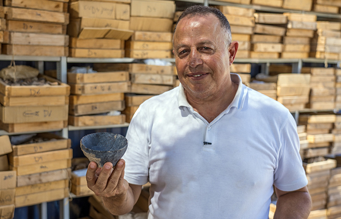 Un archeologo dell'AIA mostra una ciotola risalente al periodo neolitico. Suppellettile rinvenuto a Motza. (foto Yaniv Berman/AIA)