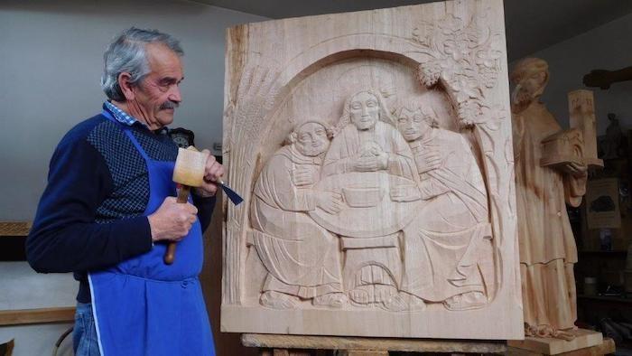 Lo scultore Willy Messner, nel suo atelier di Ortisei, mentre scolpisce uno dei due pannelli.
