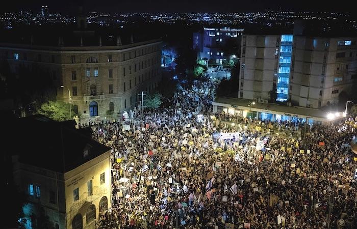 Fotografata dall'alto una delle manifestazioni serali che si succedono da mesi nei pressi della residenza ufficiale del primo ministro israeliano. In alto a sinistra la facciata del Terra Sancta College. (foto Yonatan Sindel/Flash90)