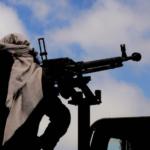 Uomo con kefiah e mitragliatore pesante su automezzo