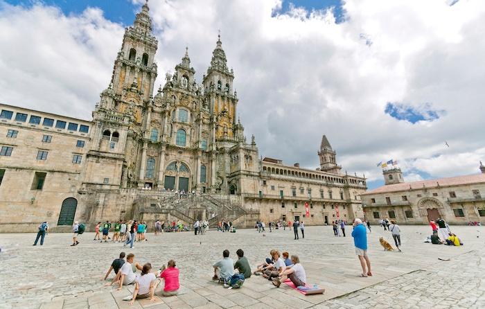 Pellegrini seduti a gruppi o in piedi contemplano la facciata della cattedrale di Santiago de Compostela dalla piazza dell'Obradoiro.